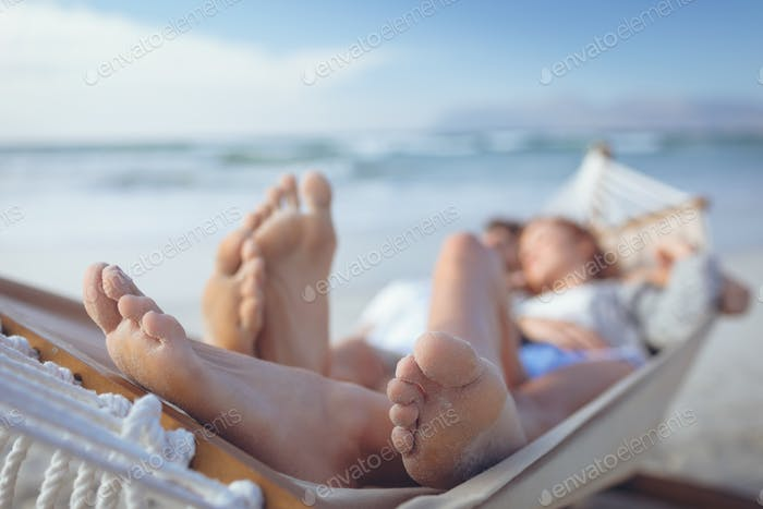 Close-up of relaxed Caucasian couple feet while they are sleeping on hammock at beach on sunny day