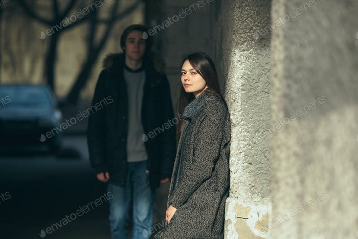 young couple standing together in front of wall