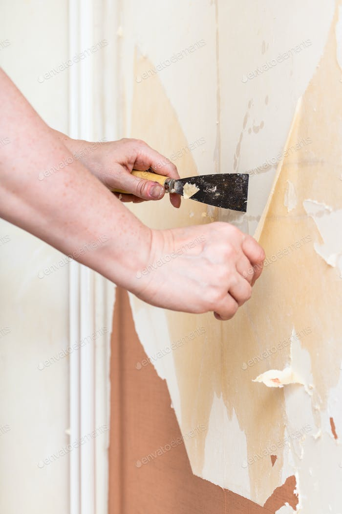 Removing of old wallpaper from wall with spatula