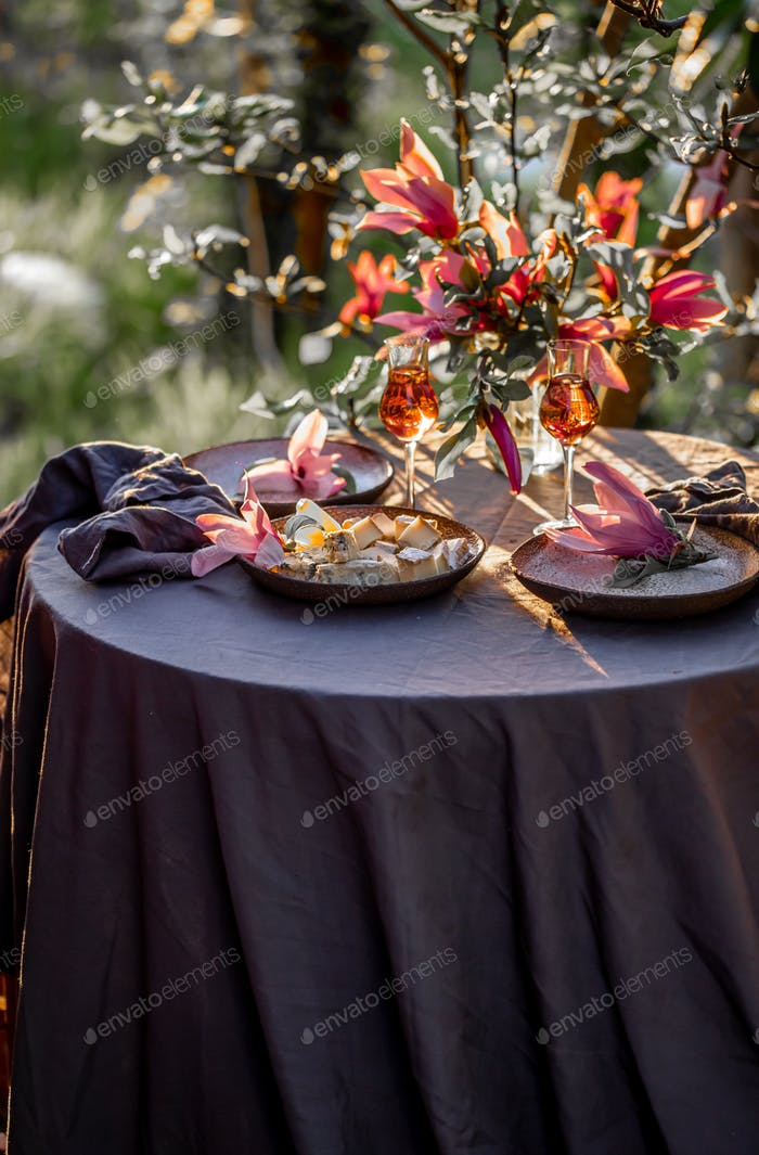 Beautiful table setting in garden on sunset light. Table decorated with magnolia flowers under