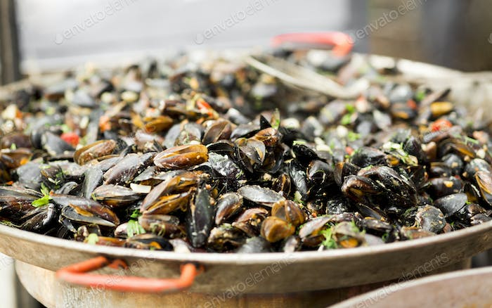 Close up of mussels in sauce in big bowl