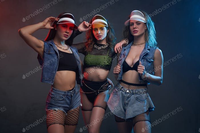Glamour young women poses in dark and colourful background