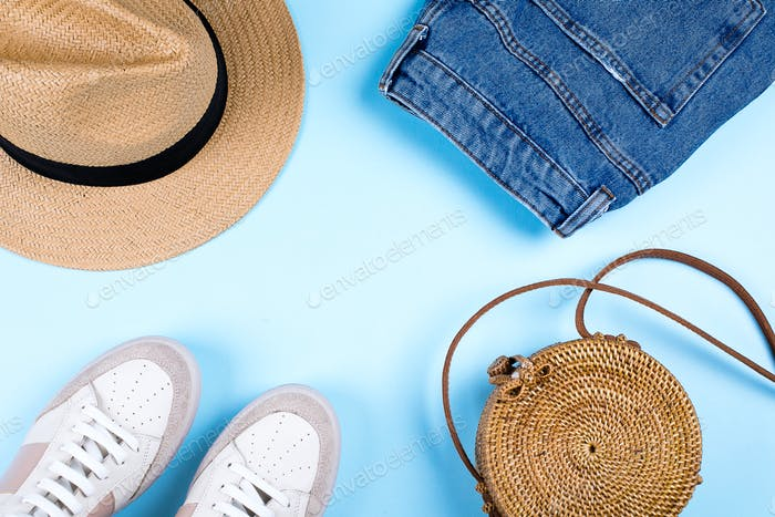 Blue jeans shorts, sneakers, hat and modern rattan bag on blue background.