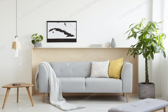 Grey lounge with cushions and blanket standing in real photo of