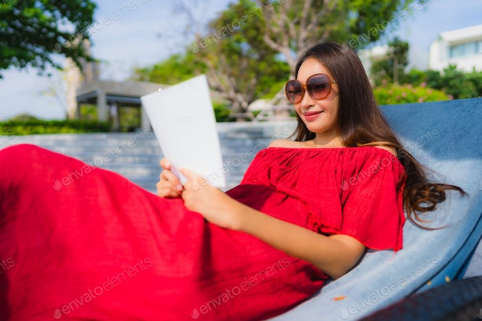 Portrait beautiful young asian woman reading book in swimming po