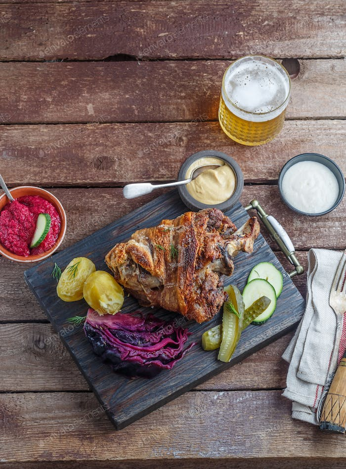 Baked pork shank with potato, cabbage and beer, copy space