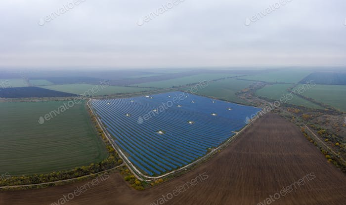 Fly over a renewable solar power plant with sun in Ukraine