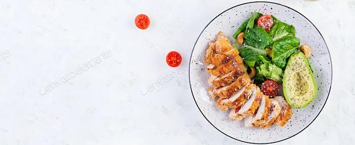 Gegrilltes Hähnchenfilet mit Salat frischen Tomaten und Avocado.