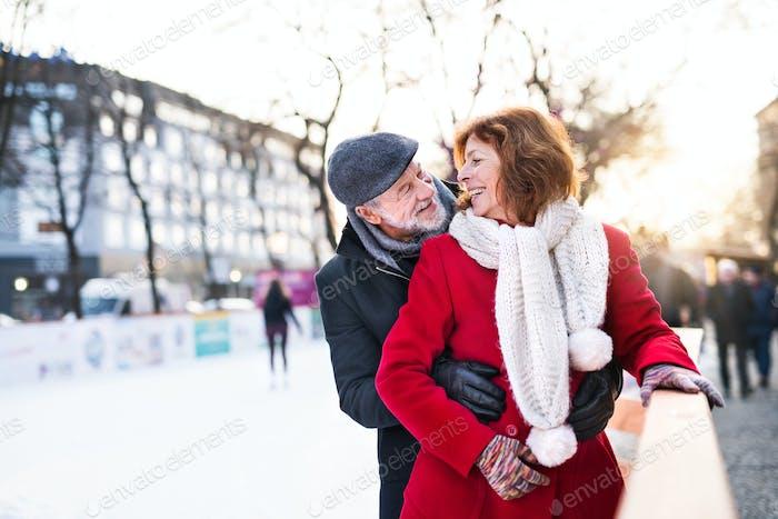 Älteres Paar auf einem Spaziergang in einer Stadt im Winter.
