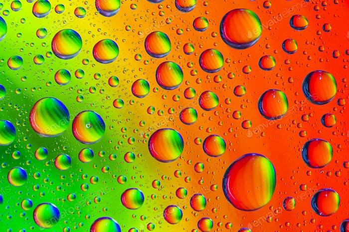 Abstrakter bunter Hintergrund mit mehrfarbigen Wassertropfen auf Glas