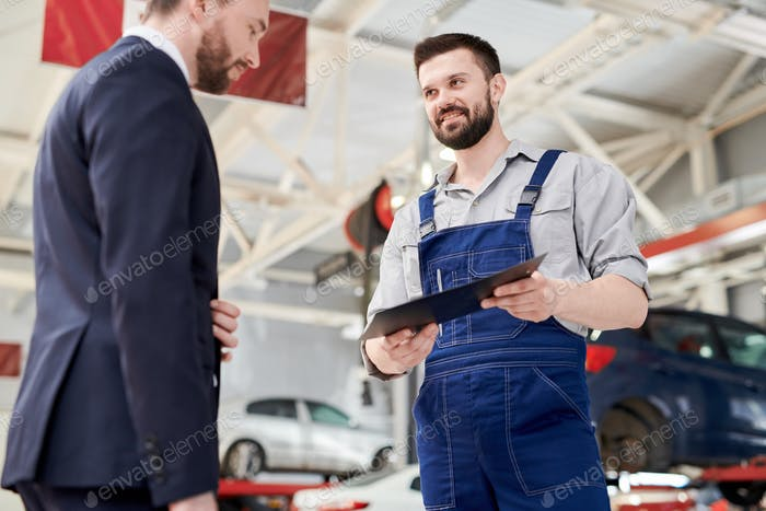 Smiling Mechanic Giving Contract to Client