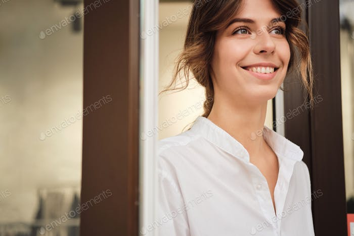 Portrait of young attractive woman happily looking away in workshop