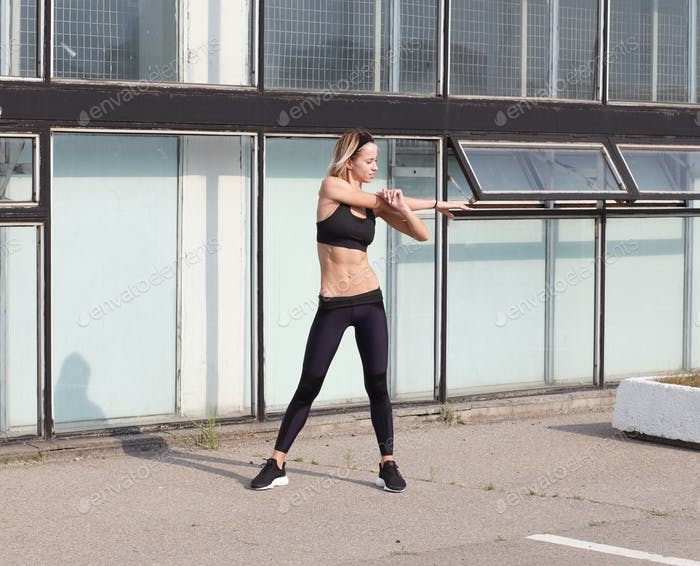 athletic woman warming up her arms before outdoor workout