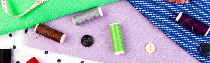 Banner of Items for sewing clothes. Sewing buttons, spools of thread and cloth.