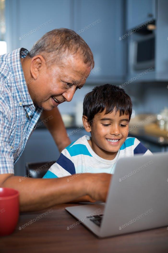 Lächelnd Großvater helfen Enkel mit Laptop
