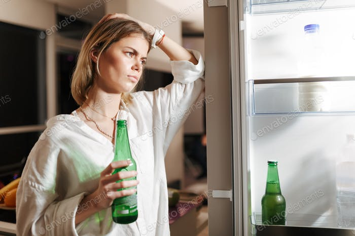 Young woman standing on kitchen at night and looking in opened fridge holding beer in hand at home