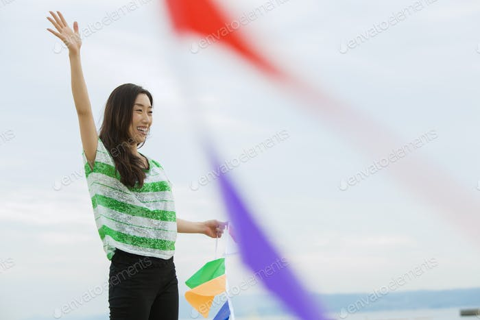A woman on a beach in Kobe hoding paper flags.
