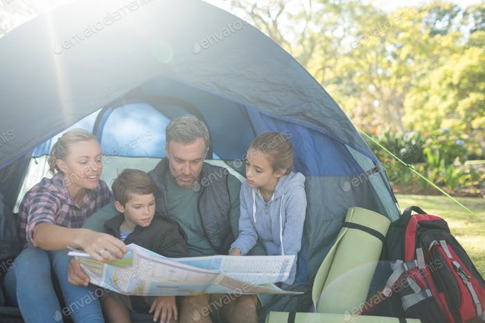 Family reading the map in tent