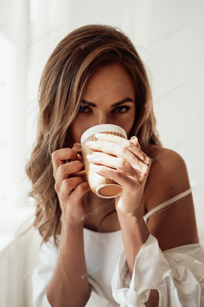 Graceful young woman in lingerie taking a sip from a cup of coffee over the white background