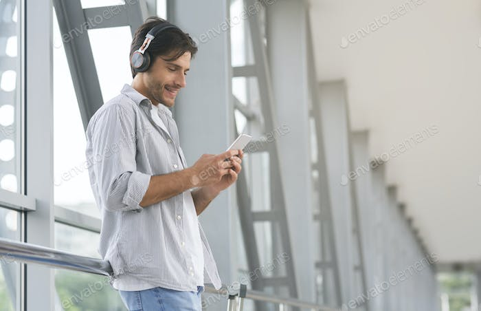 Young man in headphones choosing tracks on smartphone