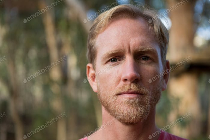Man face covered with bright sun light in forest