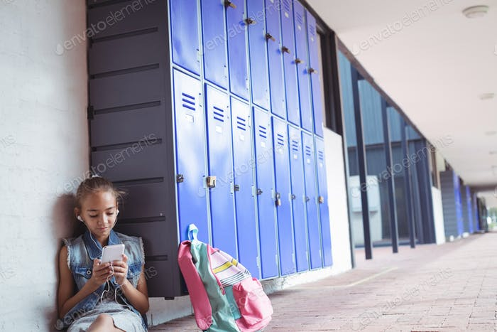 Elementary schoolgirl listening music through headphones while using mobile phone