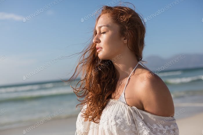 Woman with eyes closed standing standing on the beach