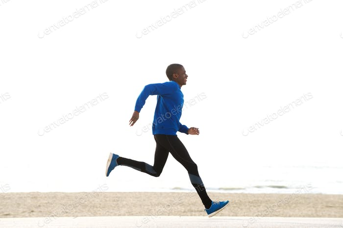 side portrait of young african american man running by the beach