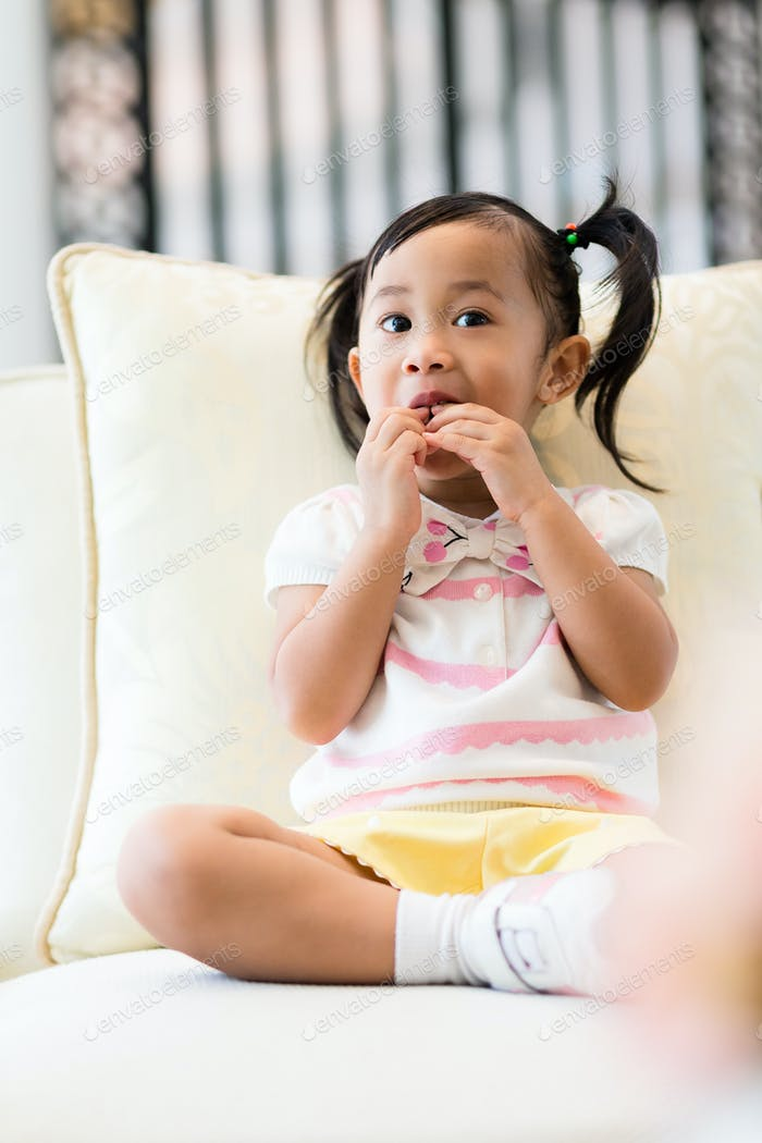 Little girl having snack and sitting on sofa