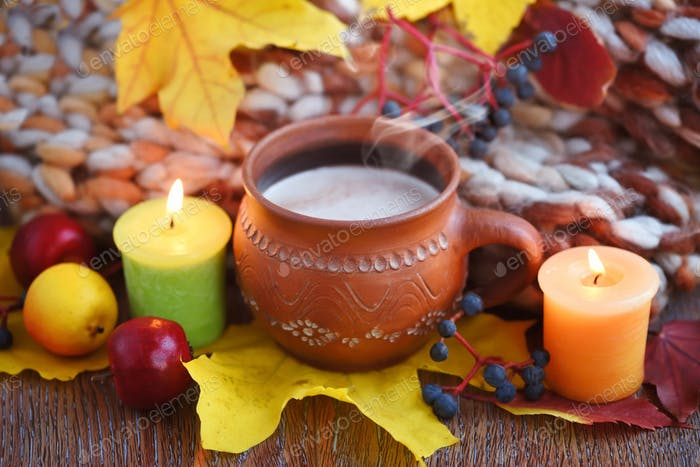 Cozy autumn composition with a cup of hot coffee, candles, fall