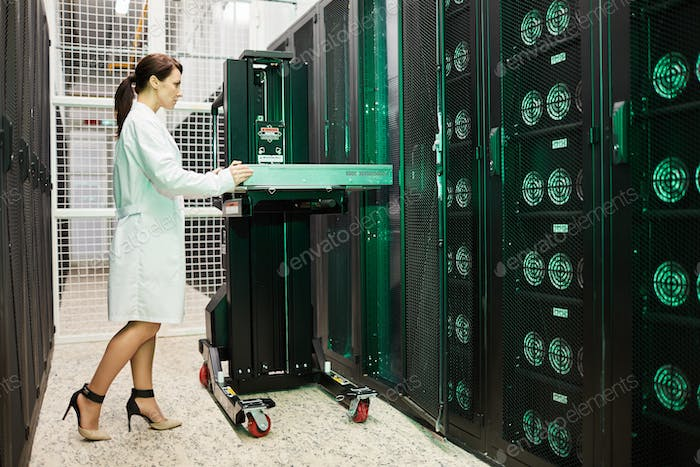 Attractive woman working in storage room of mining farm