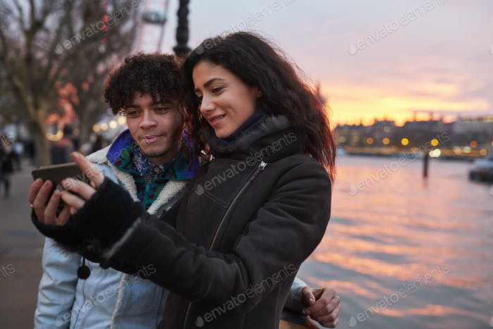 Couple Taking Selfie During Walk Along South Bank In London