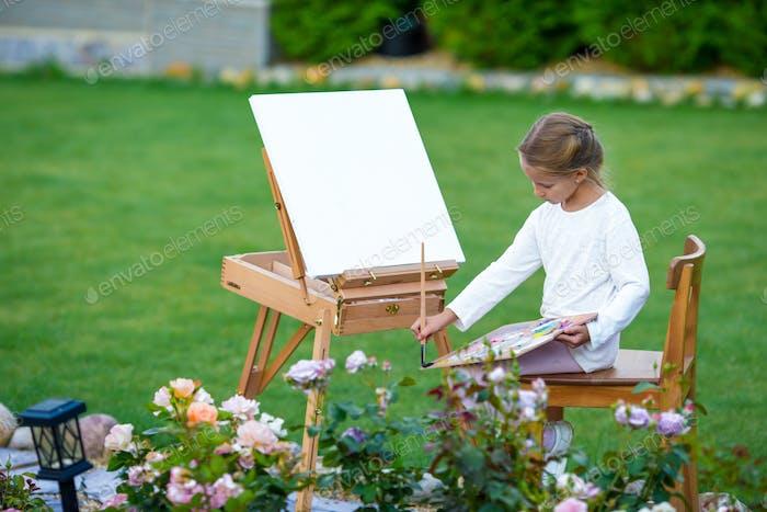 Entzückendes kleines Mädchen, das im Freien ein Bild auf Staffelei malt. Kleine Künstlerin, die auf ihr Hobby scharf  ist