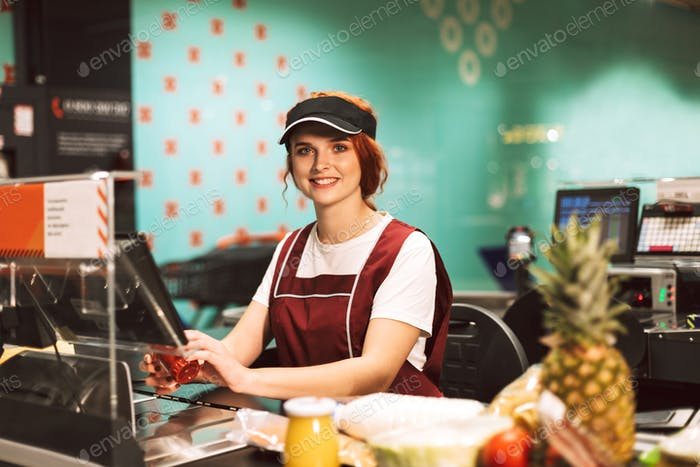 Young female cashier in uniform joyfully looking in camera while