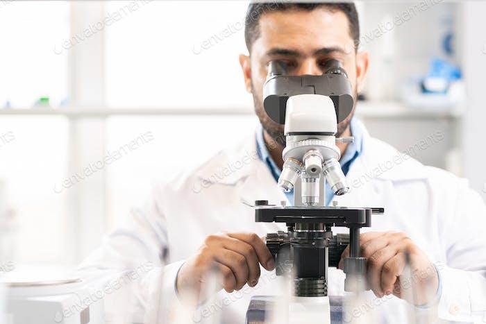 Adjusting microscope in laboratory