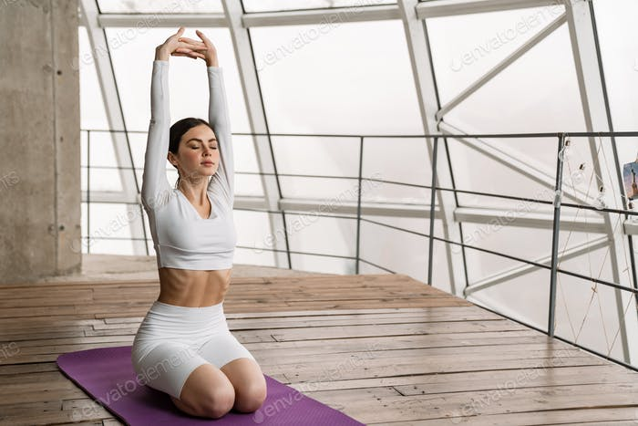Brunette peaceful woman doing exercise during yoga practice indoors