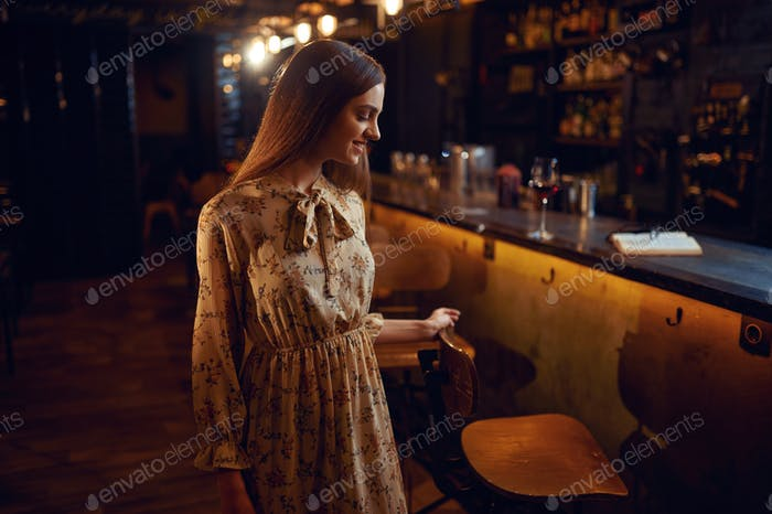 Alone woman with glass of wine sitting in bar