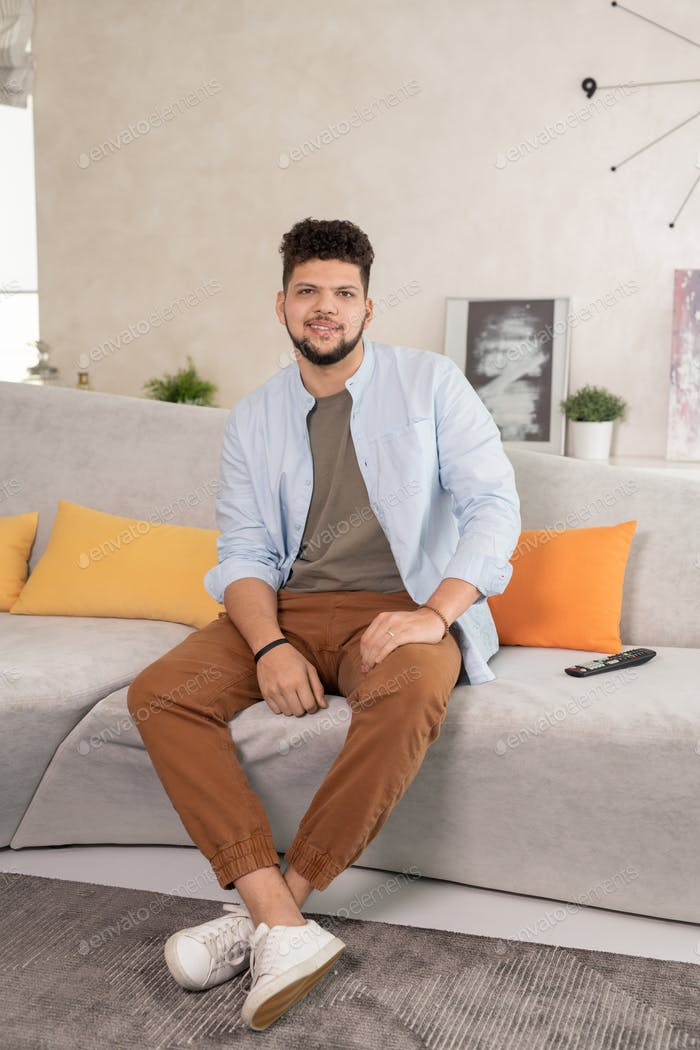 Happy young restful man sitting on couch