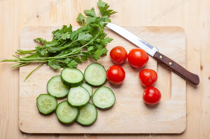 cucumber slices, parsley and tomatoes on cutting board with knife
