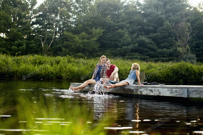 Three people,two adults and a child relaxing on a jetty,with their feet in the water