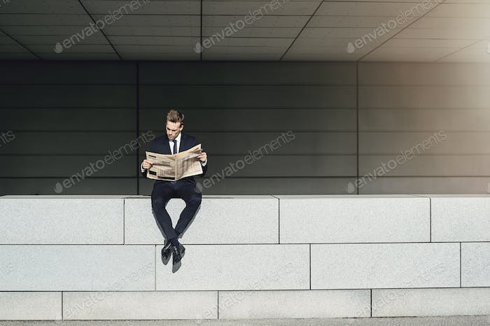 Businessman sitting on brickwall and reading newspaper