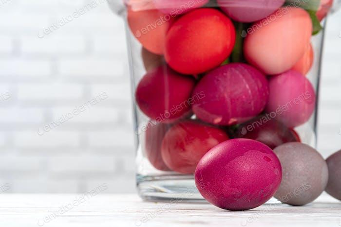 Tarro de vidrio con huevos de colores brillantes para celebración de Pascua