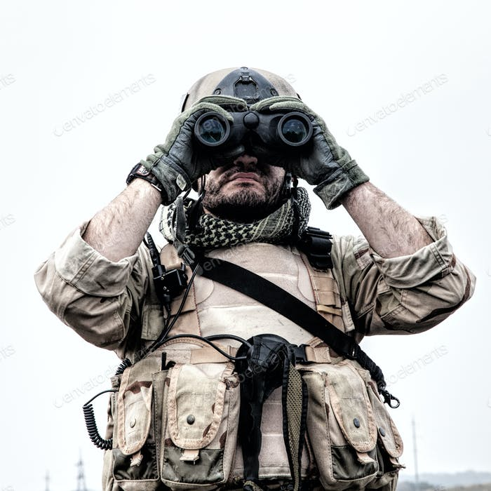 Commando soldier using binoculars to observe terrain