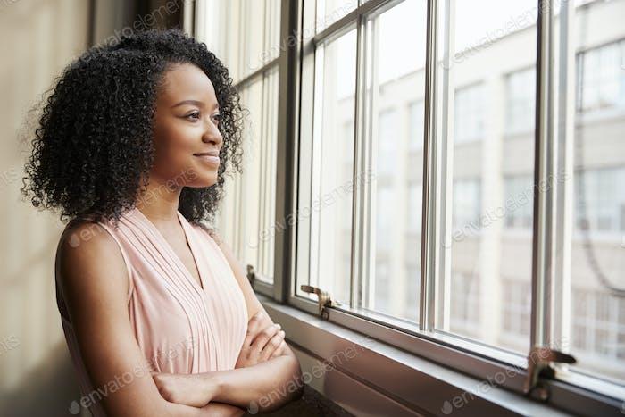 junge schwarze Frau mit Armen gekreuzt Blick aus dem Fenster