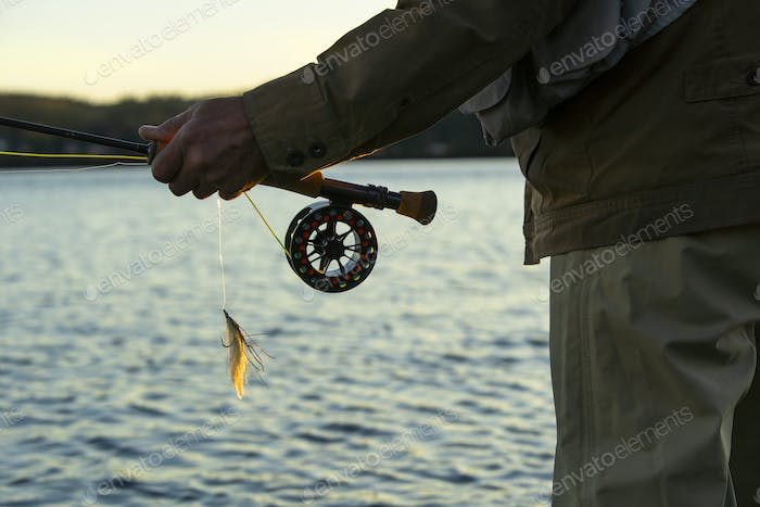 """A closeup view of the hands of a fly fisherman holding his fly rod and reel and a """"Lefty's Deceiver"""""""