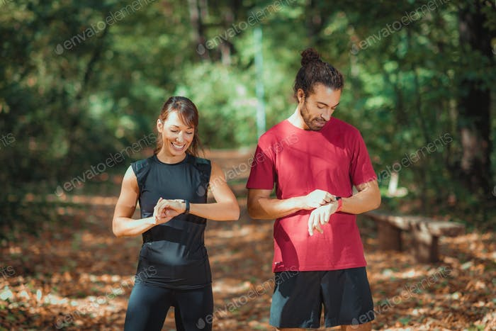 Young couple Looking at Their Smart Watches After Outdoor Training