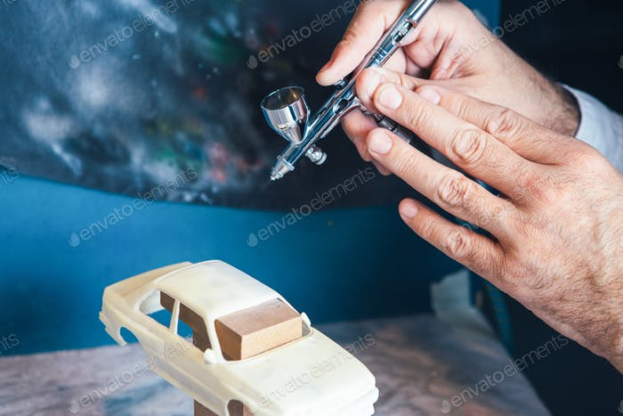 Person painting slot car with aerograph