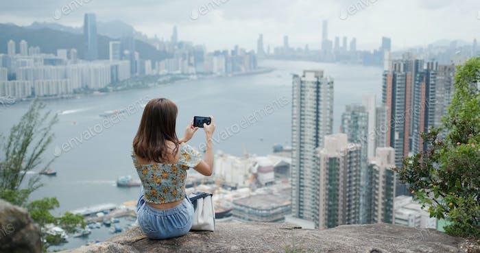 Frau sitzen auf dem Felsen und die Verwendung von Smartphones in der Stadt