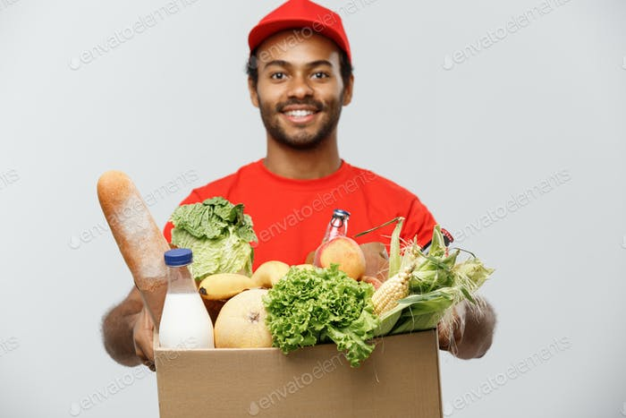 Delivery Concept - Handsome African American delivery man carrying package box of grocery food and