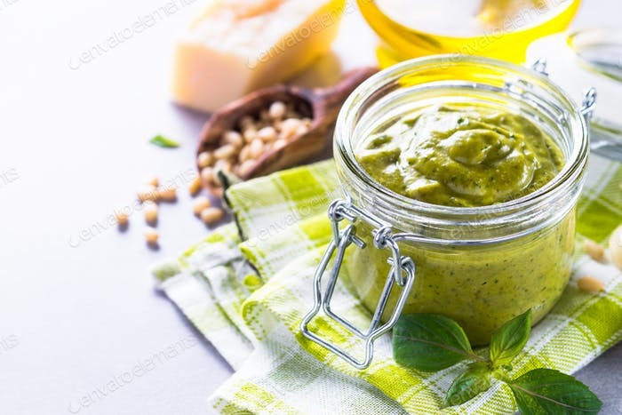 Pesto sauce in glass jar and ingredients.